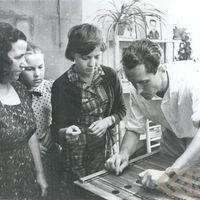 Folklorist Kārlis Arājs tuning a musical instrument